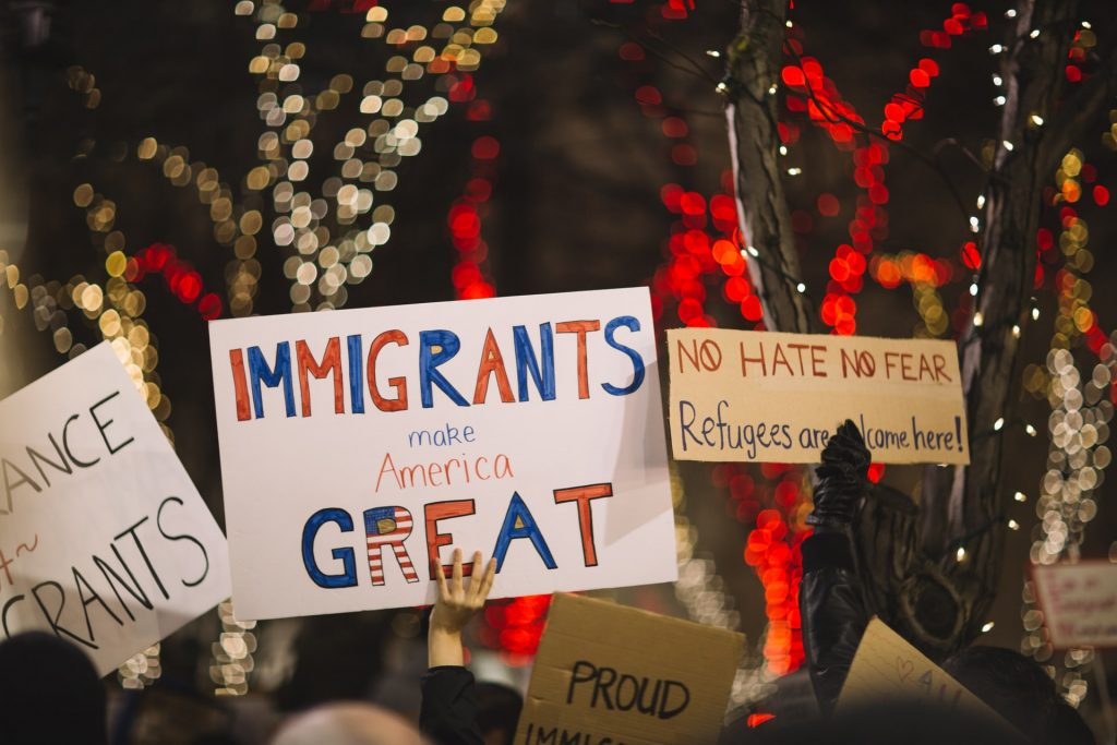 """People holding signs at a protest or rally that say """"immigrants are great"""" - Bipartisan Agreement Proved Elusive in 2017 Immigration Negotiations"""