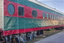 red and green vintage railroad passenger car on a sidetrack