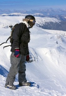 The snowboarder-freerider is standing on the brink of a precipice and looking down.