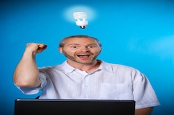 man wih a beard with a light bulb on the laptop