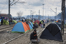 Idomeni, Greece - March 17, 2016: Refugees from Syria sit by their tents on March 17, 2015 in the refugee camp of Idomeni.