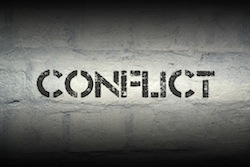 conflict stencil print on the grunge white brick wall
