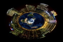 Bright city lights on miniature planet illustrates concept of growing energy usage on our earth's shrinking resources. Earth Day and Earth Hour concepts.