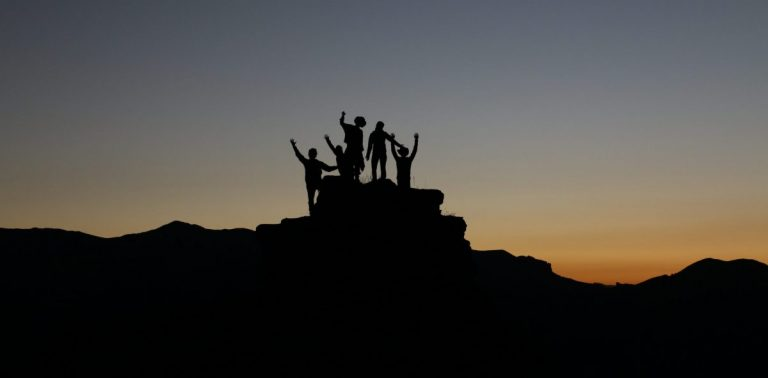 ethical leadership and Effective Leadership as portrayed by people standing on a rock with their fists in the air