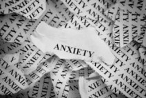 "Torn pieces of paper with the word ""Anxiety"". Concept Image. Black and White. Close-up."